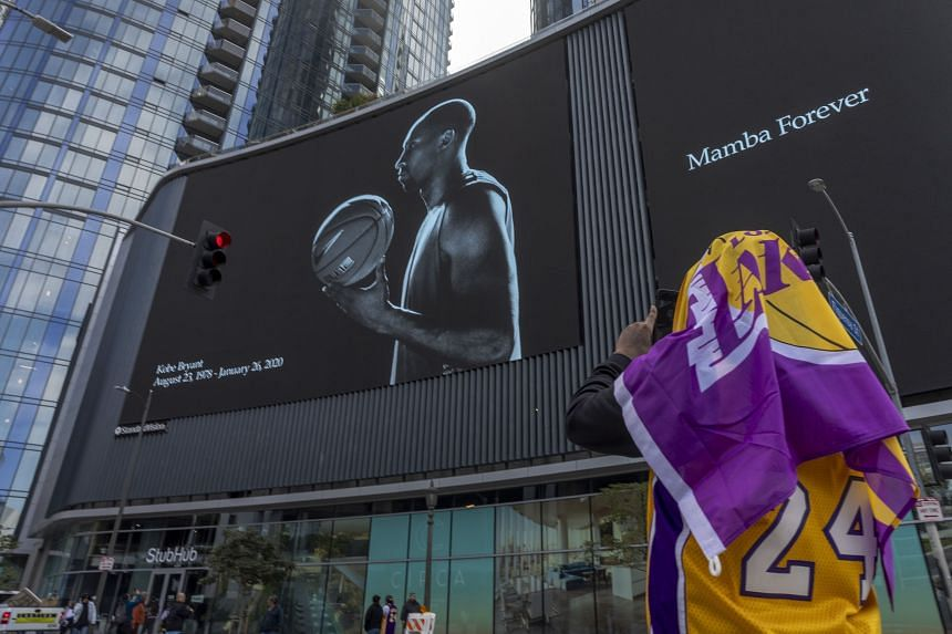 A fan photographs a mural memorialising former NBA star Kobe Bryant, who was killed in a helicopter crash in California, near the Staples Center, on Jan 27, 2020.