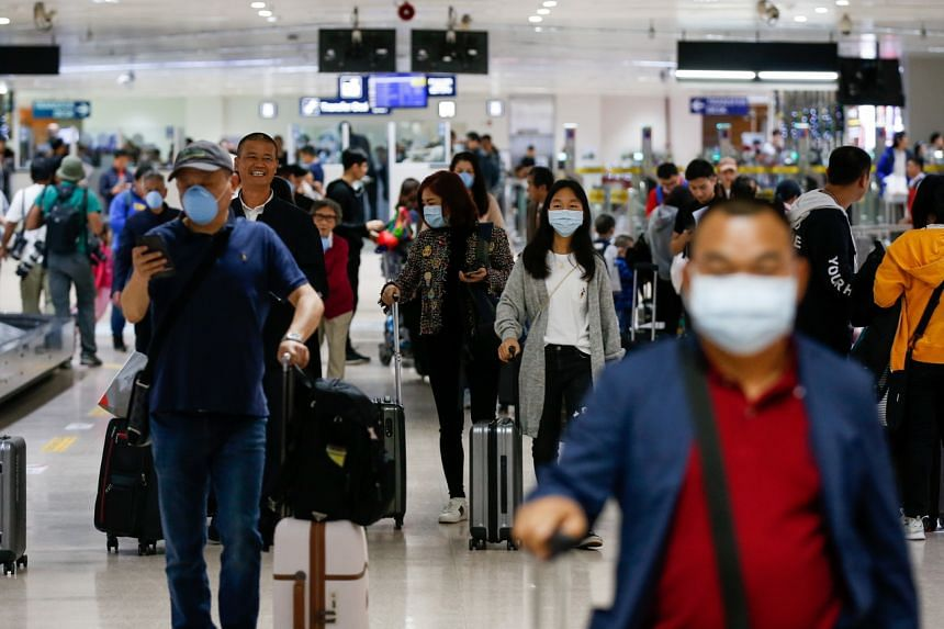 Passengers wearing face masks who arrived from Guangzhou, China prepare to exit the airport at the Ninoy Aquino International Airport in Manila, Philippines on Jan 22, 2020.