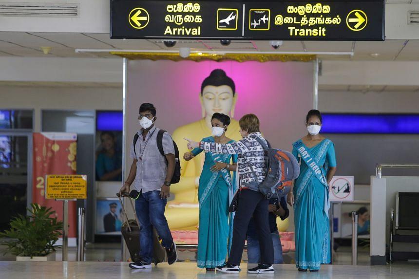Sri Lankan airport officials and passengers wears protective masks at the Bandaranaike International Airport in Colombo, Sri Lanka, on Jan 24, 2020.