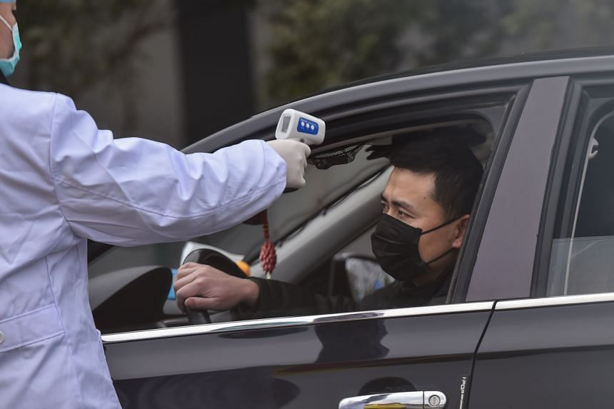 A police takes the temperature of a driver at a checkpoint on a street on the outskirts of Wuhan on Jan 27, 2020.