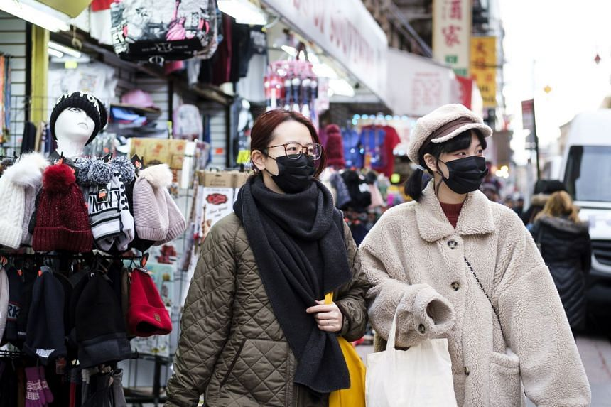 People wearing masks in the Chinatown neighbourhood of New York on Jan 27, 2020. Since China has suspended all flights out of Wuhan, there are fewer travellers from there arriving in the US.