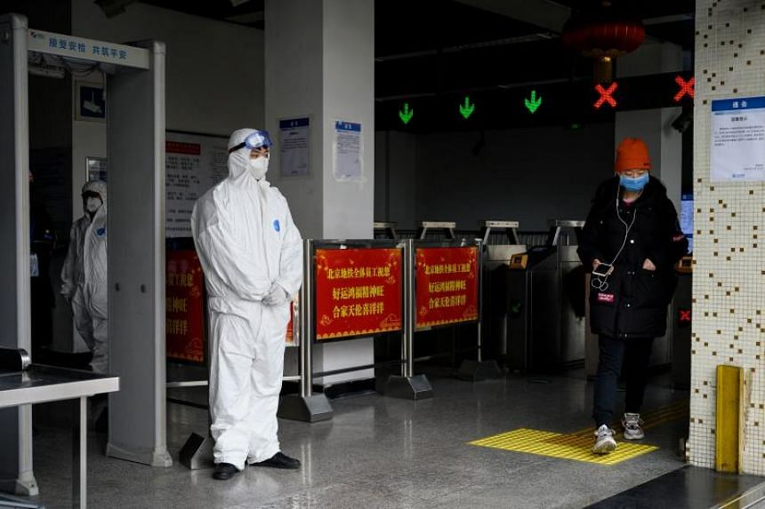 Security personnel at the entrance of a subway station in Beijing on Jan 28, 2020.
