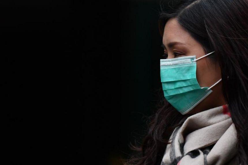 A pedestrian wears a surgical mask in London on Jan 24, 2020.