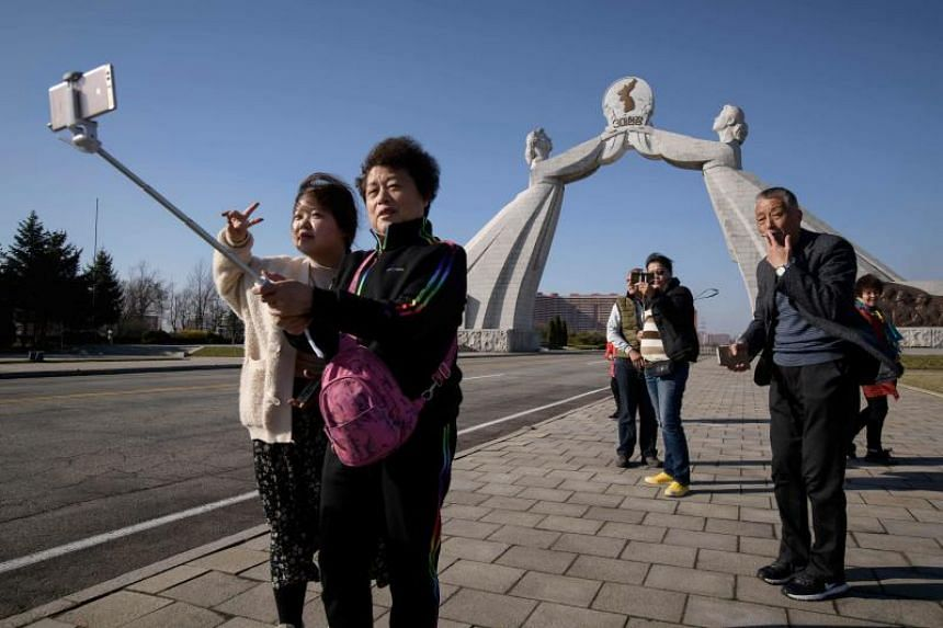 A photo taken on April 15, 2019, shows tourists from China at the Three Charters monument in Pyongyang.