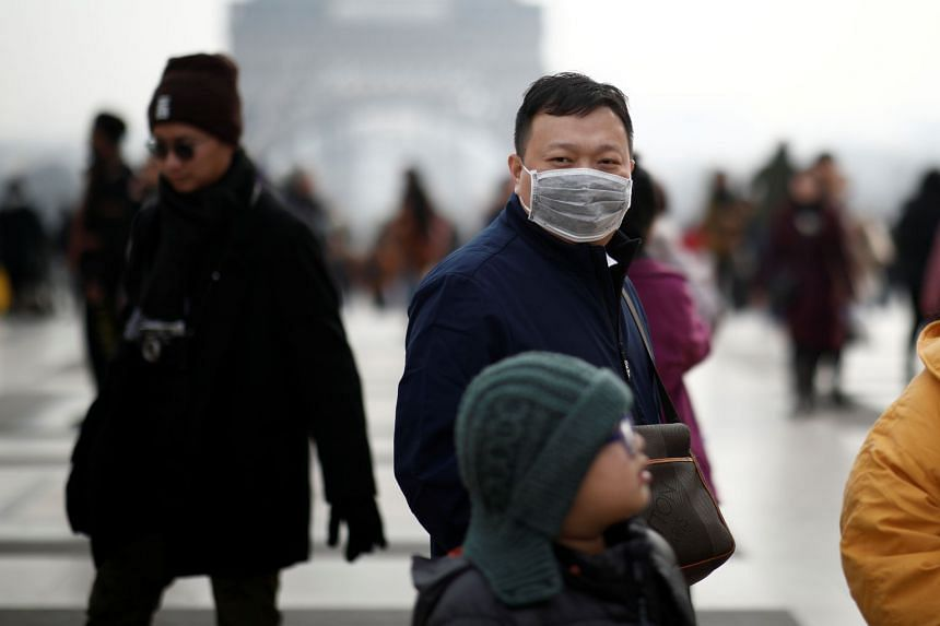 A man wears a face mask on the Trocadero esplanade in front of the Eiffel Tower in Paris.