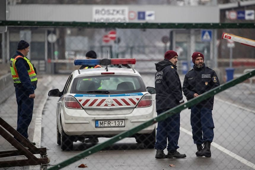 Hungarian police officers secure the Hungary-Serbia border crossing of Roszke as seen from Horgos, Serbia.