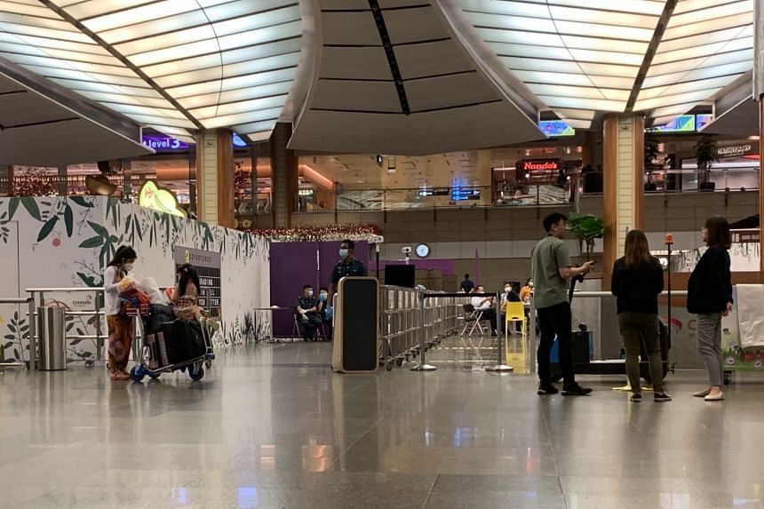 Passengers (left) waiting to check in at a designated but unmarked check-in counter at Changi Airport's Terminal 2, set up for people boarding a Scoot flight to Wuhan, on Jan 29, 2020.