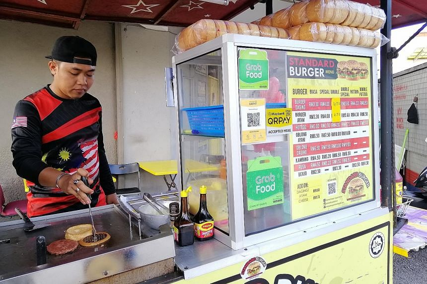 A roadside burger stall in Kuala Lumpur that accepts e-wallet payments. As part of its drive to promote e-payments, the Malaysian government is collaborating with GrabPay, Touch 'n Go eWallet and Boost to give RM30 worth of free shopping money for ea