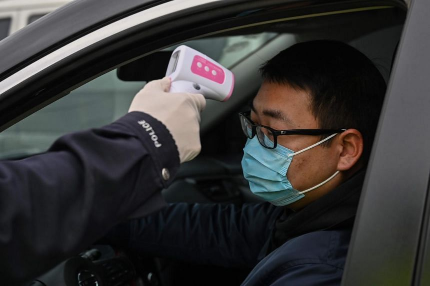 A police officer takes the temperature of a driver at a checkpoint in Wuhan, China, on Jan 27, 2020.