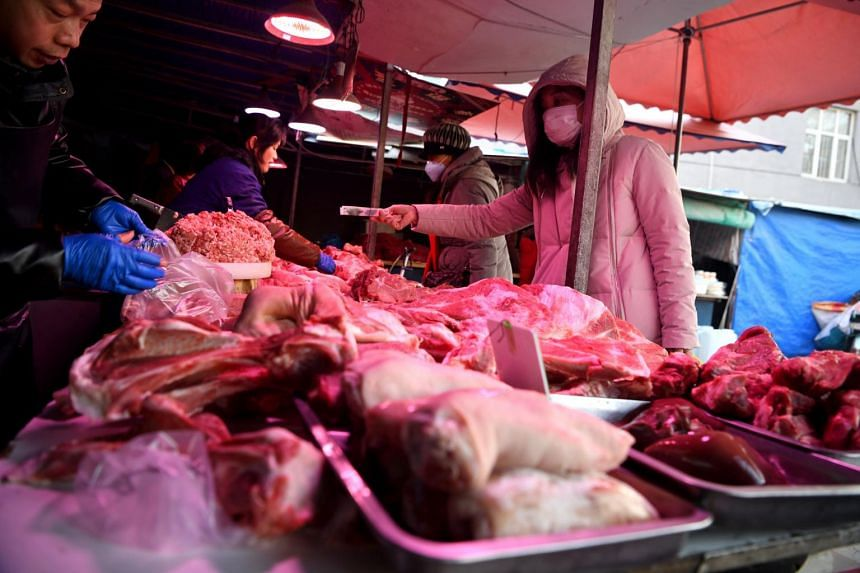 Customers wearing protective masks buying meat at a market in Beijing, China, on Jan 23, 2020.