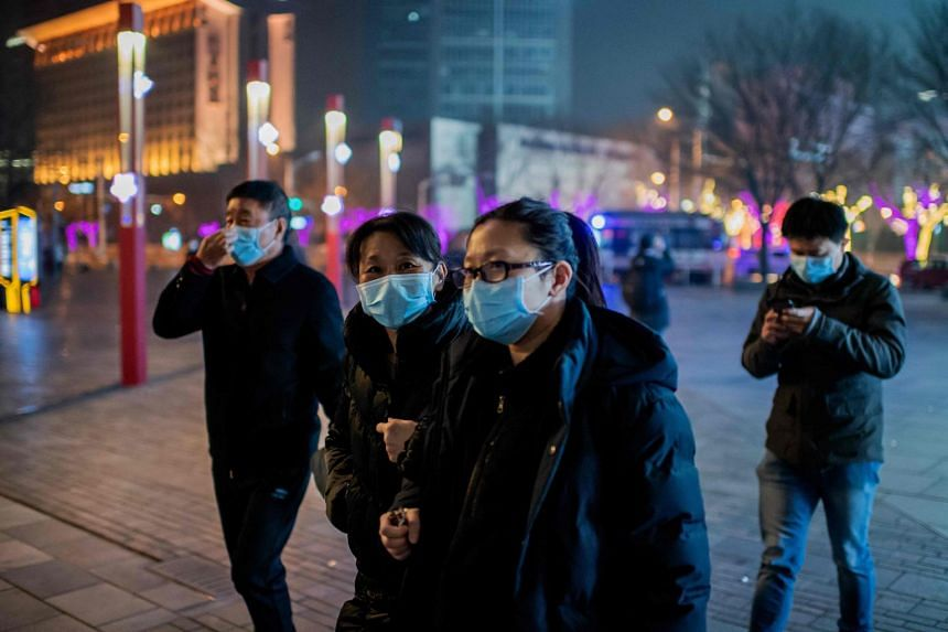 People wearing protective masks to help stop the spread of a deadly virus in the Sanlitun area in Beijing on Jan 28, 2020.