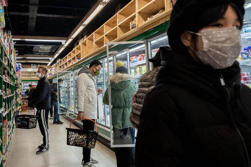 People wearing protective masks shop for groceries at a supermarket in Beijing on Jan 28, 2020.