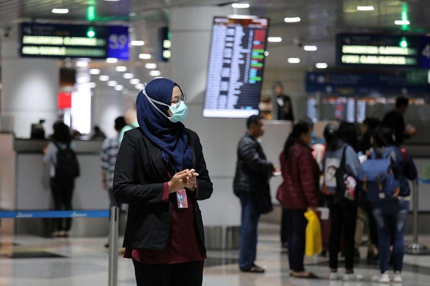 An aviation officer wearing a mask at Kuala Lumpur International Airport in Sepang, Malaysia, on Jan 21, 2020.