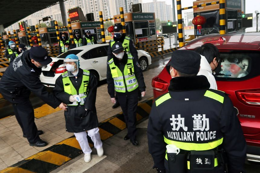 Police officers at an expressway toll station in Xianning, a city bordering Wuhan in Hubei province, China, on Jan 24, 2020.