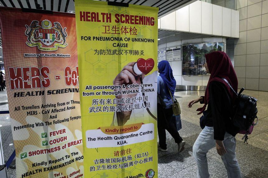 Passengers walking past a poster about coronavirus screening at the Kuala Lumpur International Airport in Sepang, Malaysia, on Jan 21, 2020.