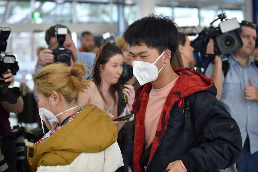 Passengers wearing masks arrive at Sydney airport after arriving on a plane from Wuhan on Jan 23, 2020.