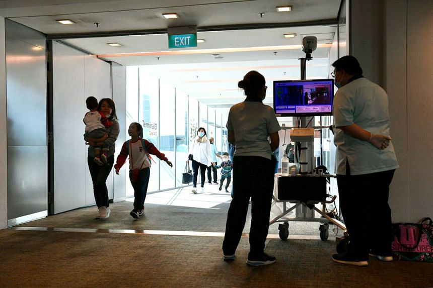 Travellers going through a thermal scanner at Changi Airport's Terminal 3 after arriving from Hangzhou on Jan 22, 2020.