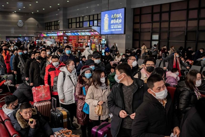 Travellers with protective masks lining up before boarding their train at the Beijing West Railway Station on Jan 24, 2020, as they travel for the Chinese New Year holidays.