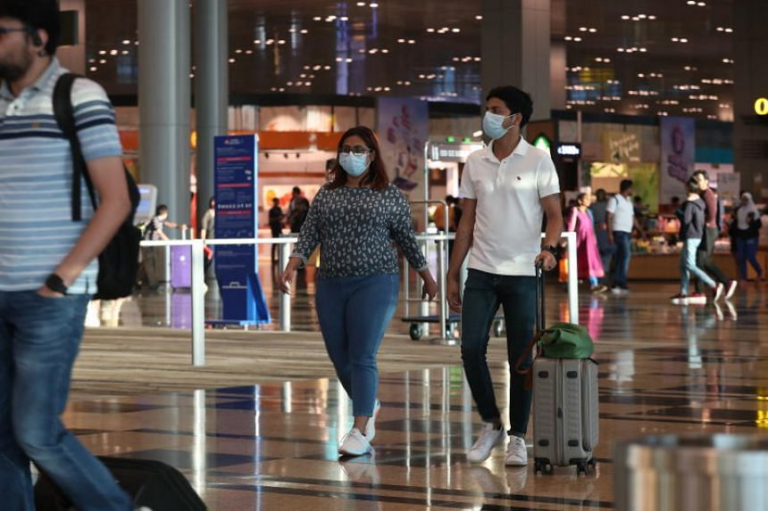 People are seen wearing masks as they walk through Changi Airport's Terminal 3 on Jan 25, 2020.