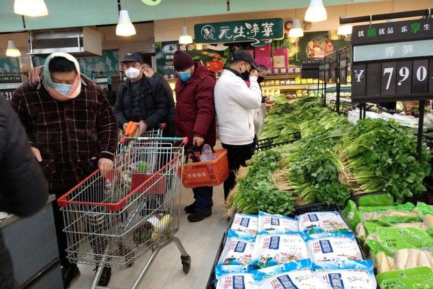 Customers with face masks on shopping at a supermarket on the second day of the Chinese New Year on Jan 26, 2020, in Wuhan, China.