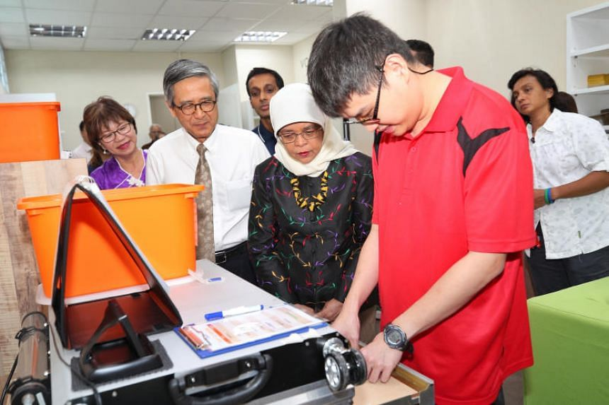 President Halimah Yacob, with Autism Resource Centre president Denise Phua (far left) and Autism Association chairman Ho Swee Huat, watching Mr Davin Yeap, 30, operate a laser cutting machine on Jan 29, 2020.
