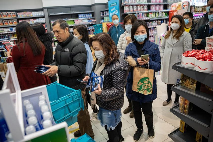 Customers line up to buy face masks in a Watsons store in Hong Kong on Jan 29, 2020.