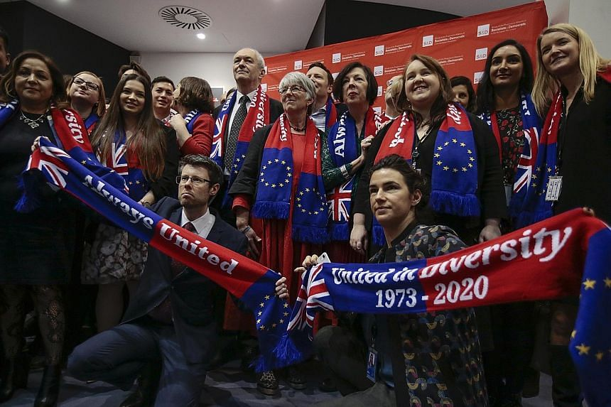 British Members of the European Parliament with red-and-blue scarves with EU and British flags on them ahead of their last plenary session of the EU Parliament in Brussels yesterday.