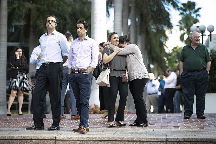 People in Miami, Florida, waiting outdoors on Tuesday after high-rise buildings shook as a major earthquake struck south of Cuba.