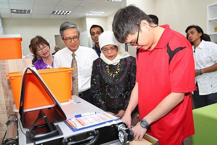 President Halimah Yacob, Autism Association chairman Ho Swee Huat and Autism Resource Centre president Denise Phua, who is also an MP for Jalan Besar GRC, observing Mr Davin Yeap operate a laser cutting machine at the Eden Centre for Adults in Clemen