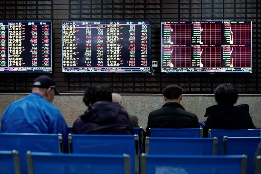 Investors looking at screens showing stock information at a brokerage house in Shanghai, China, on Jan 16, 2020.