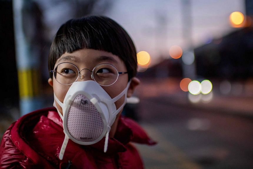 A child wearing a protective mask looks on in Beijing on Jan 29, 2020.