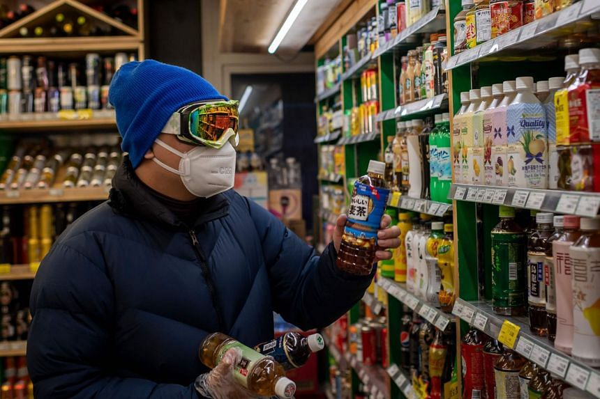 A man wearing a protective mask, goggles and gloves shopping at a Beijing supermarket on Jan 30, 2020.