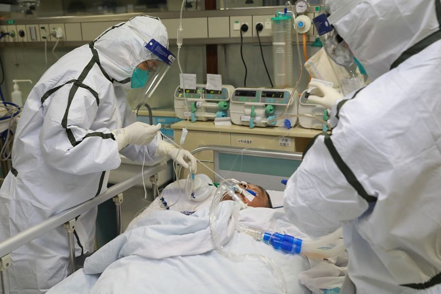 Medical staff in protective suits treat a patient with pneumonia caused by the new coronavirus at the Zhongnan Hospital of Wuhan University, on Jan 27, 2020.
