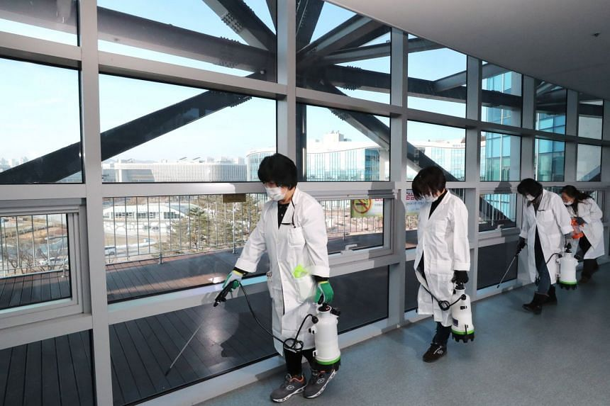 Quarantine officials spray disinfectant in a hallway at a government complex in Sejong, South Korea, on Jan 30, 2020.