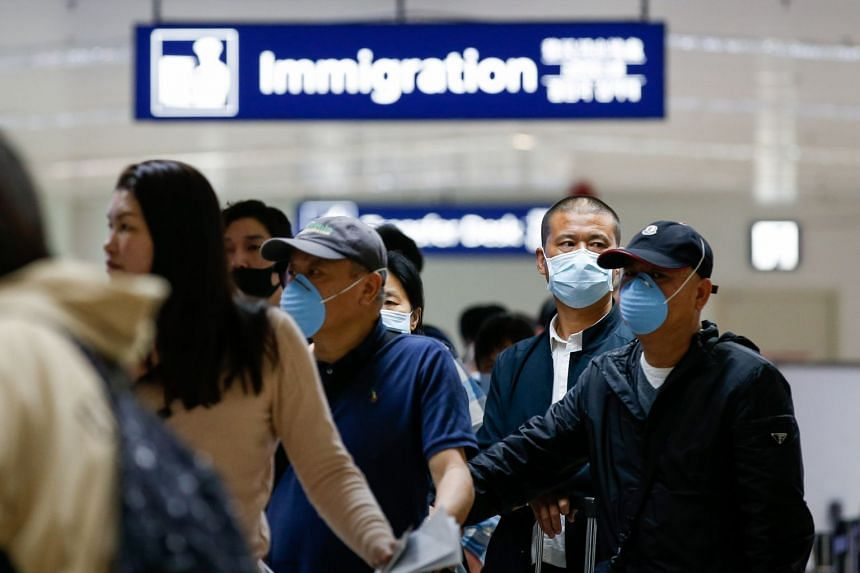 Passengers wearing face masks who arrived from China's Guangzhou line up for immigration at the Ninoy Aquino International Airport in Manila, on Jan 22, 2020.