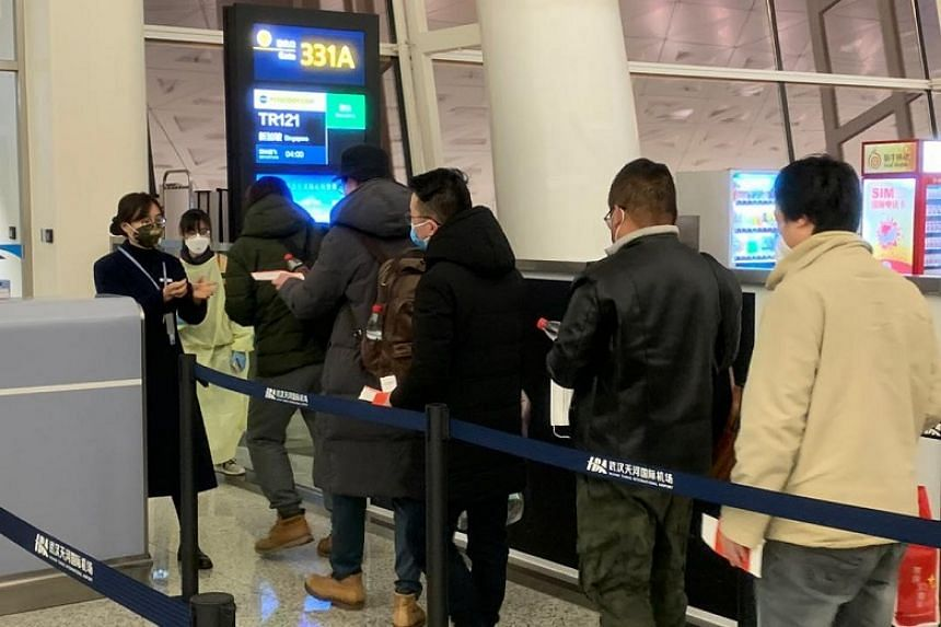 Passengers queueing to board the flight to Singapore at Wuhan airport. The MFA said the returning Singaporeans will undergo medical screening upon arrival at Changi Airport.