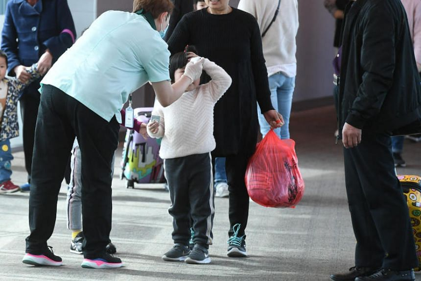 A child having her temperature checked by a border screener at Changi Airport's Terminal 3, on Jan 22, 2020.