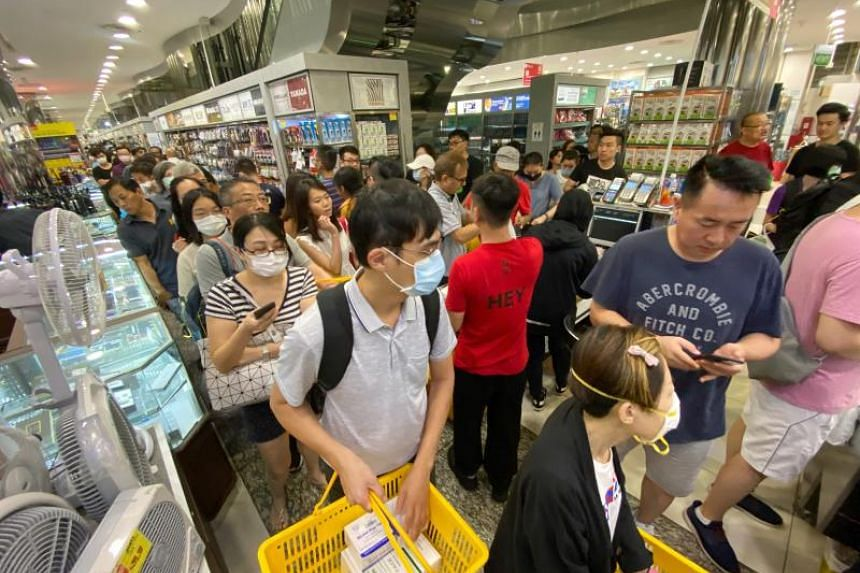 Customers queue to buy face masks costing $9.90 for a box of 50 masks at Mustafa store on Jan 28, 2020.