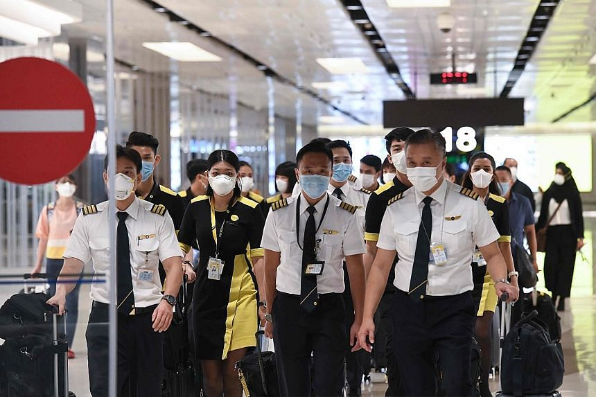 The crew of the chartered Scoot flight that evacuated Singaporeans from Wuhan arriving at Changi Airport yesterday. Scoot said surgical masks were given to all passengers, and the crew had to wear N95 masks and surgical gloves on board. Labour chief