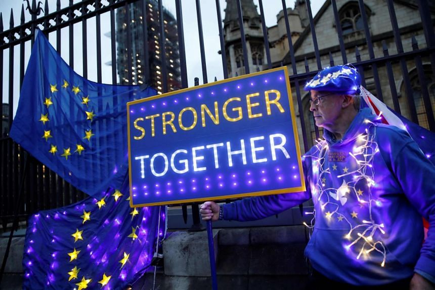 An anti-Brexit protester displays illuminated EU flags near the Houses of Parliament in London on Jan 30, 2020.