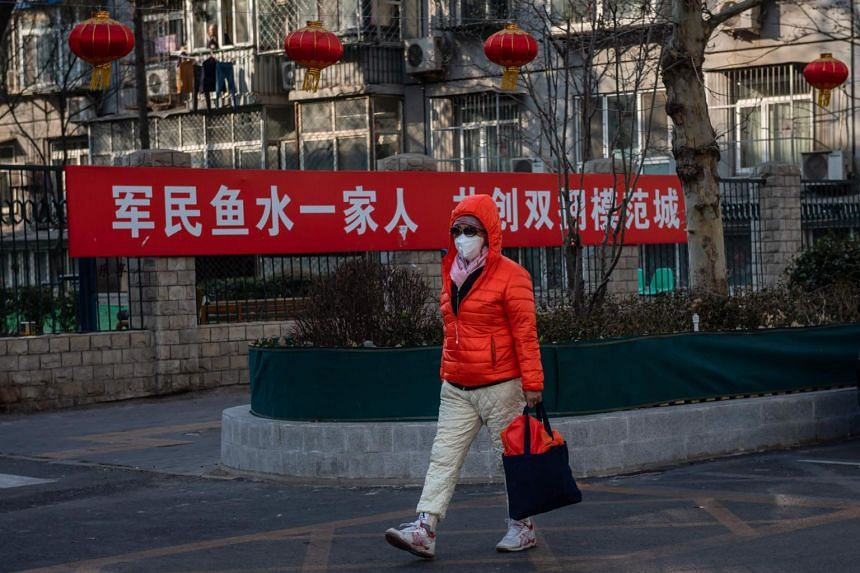 A woman wearing a protective mask while walking on an empty road in Beijing, China, on Jan 29, 2020.