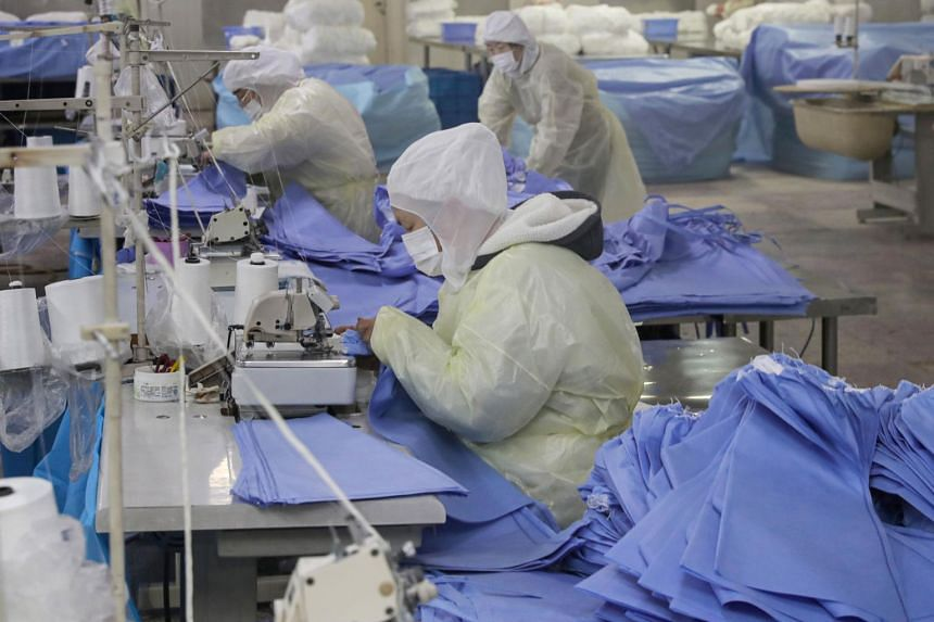 Workers produce protective suits at a factory in Nantong, China, on Jan 27, 2020.
