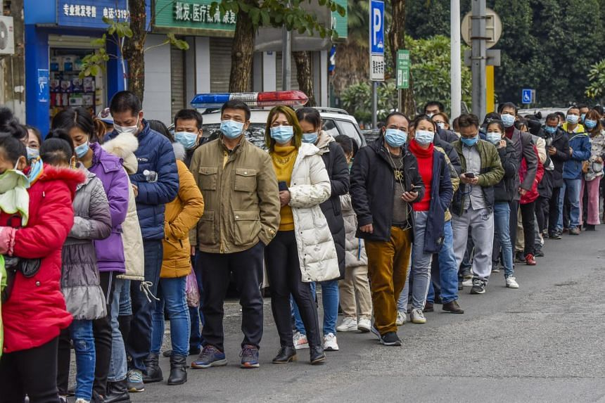 Residents forming a long queue to buy masks at a medical company in Nanning, Guangxi, China, on Jan 29, 2020.