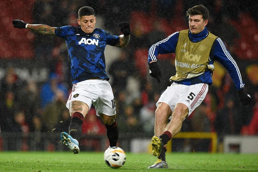 Rojo (left) and United's Harry Maguire warm up ahead of a match.