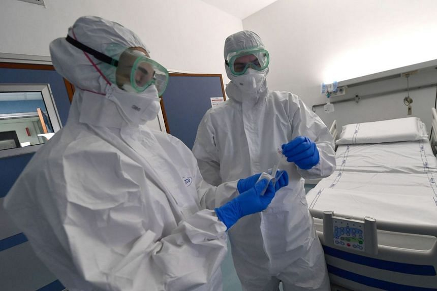 Medical staff in an isolation room of a hospital in Genoa, Italy, on Jan 30, 2020.