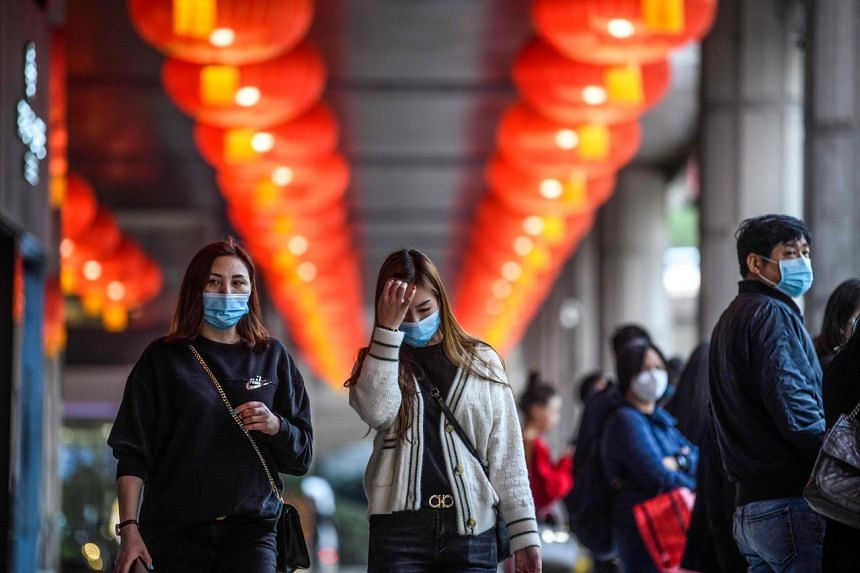 Pedestrians wear face masks as they walk outside the New Orient Landmark hotel in Macau on Jan 22, 2020. Hong Kong and Macau are two of the cities hardest hit by the drop in Chinese travel and spending.