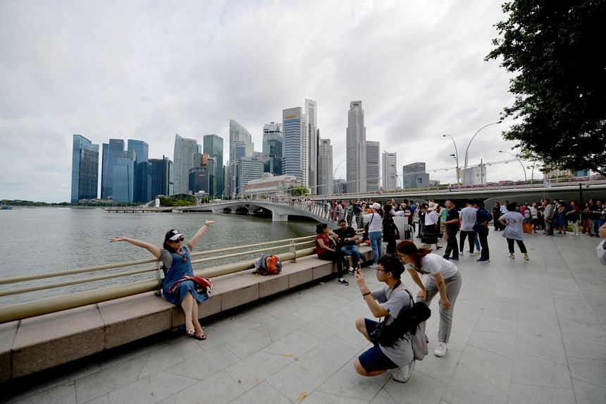 Singapore Skyline and Central Business District with tourists in the backdrop.