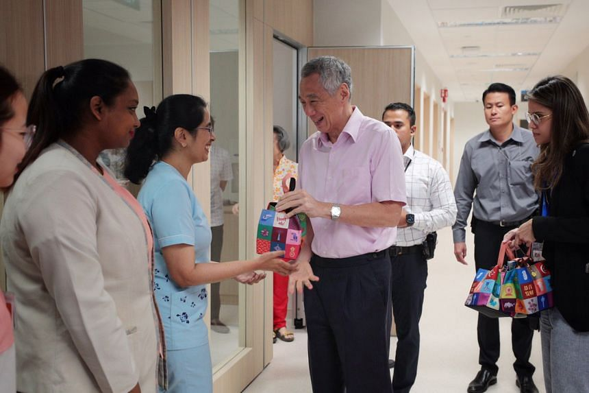 Prime Minister Lee Hsien Loong gives out oranges to Clinic J nurse manager Imrana Banu Khider Mohamed, 34, and other NCID front-line staff during his visit there on Jan 31, 2020.