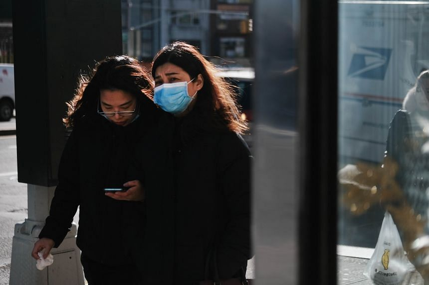 People wear medical face masks on the streets of Chinatown in New York, on Jan 29, 2020.