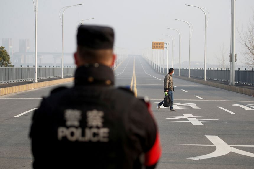 A man arriving from China's Hubei province approaches a checkpoint at the Jiujiang Yangtze River Bridge in Jiangxi province on Jan 31, 2020.